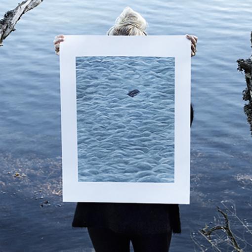 poster : une femme se tient au bord d'un lac et tient dans ses mains un poster représentant la mer et une baleine